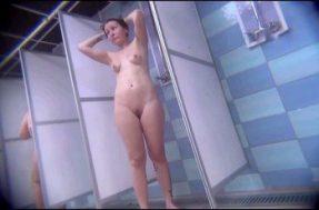 Молодая женщина с татуировкой на ноге моется в душе
